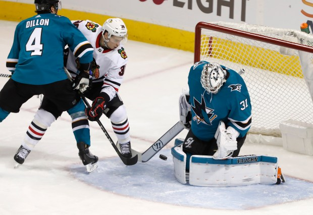 San Jose Sharks goaltender Martin Jones (31) blocks a shot in front of Chicago Blackhawks' Matthew Highmore (36) and San Jose Sharks' Brenden Dillon (4) in the second period at the SAP Center in San Jose, Calif., on Thursday, March 1, 2018. (Nhat V. Meyer/Bay Area News Group)