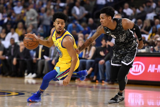 Golden State Warriors' Quinn Cook (4) drives past San Antonio Spurs' Dejounte Murray (5) during the second quarter of their NBA game at the Oracle Arena in Oakland, Calif., on Thursday, March 8, 2018. (Jose Carlos Fajardo/Bay Area News Group)