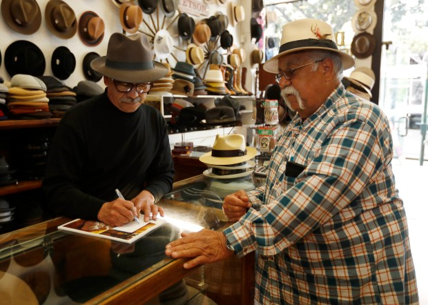 Alfredo Diaz, left, owner of Diaz Menswear, helps Juan Palacios, a customer for over 30 years, with a shoe order, at Diaz Menswear in downtown San Jose, Calif., on Wednesday, March 21, 2018. (Nhat V. Meyer/Bay Area News Group)