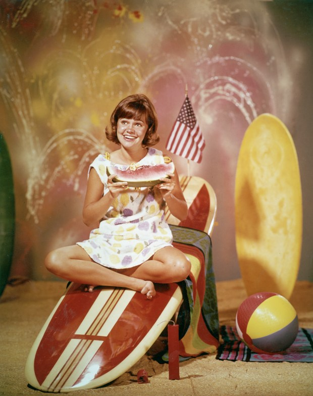 Promotional portrait of American actor Sally Field sitting on a wooden surfboard with an American flag and eating a watermelon, for the television series, 'Gidget,' circa 1965. (Photo by ABC Television/Getty Images)