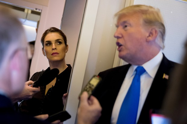 President Donald Trump, accompanied by President Donald Trump's White House Communications Director Hope Hicks, second from left, speaks to reporters aboard Air Force One at Ninoy-Aquino International Airport in Manila, Philippines, Tuesday, Nov. 14, 2017, before traveling to Hickam Air Force Base, Hawaii and then on to Washington. Trump is wrapping up a five country trip through Asia traveling to Japan, South Korea, China, Vietnam and the Philippines. (AP Photo/Andrew Harnik)
