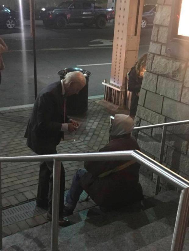 This photo provided by Caleb Baca shows former Vice President Joe Biden talking and writing a note to a homeless man outside a movie theater in the Georgetown section of Washington D.C. on March 8, 2018. (Caleb Baca via AP)