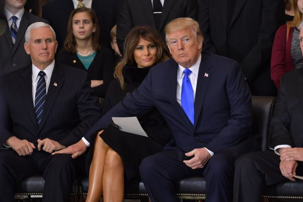 TOPSHOT - President Donald Trump (R)reaches for Vice President Mike Pence as US First Lady Melania Trump looks on, during the memorial service for Reverend Billy Graham in the Rotunda of the US Capitol on February 28, 2018 in Washington, DC. / AFP PHOTO / Mandel NGAN (Photo credit should read MANDEL NGAN/AFP/Getty Images)