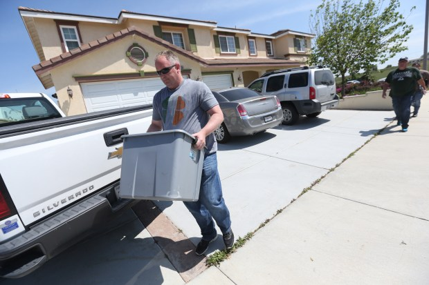 An agent walks away with a box from the home of Nasim Aghdam's parents in Menifee, Calif., on Wednesday, April 4, 2018. Aghdam was the shooter at the YouTube headquarters in San Bruno Tuesday.   (Stan Lim/Southern California News Group)