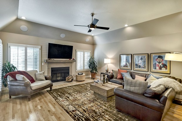 The family room features a wood-burning fireplace, shelving and a bar area.