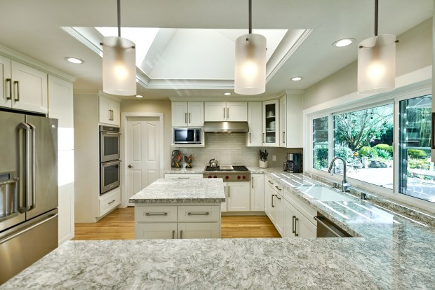 The home's glistening gourmet kitchen comes with Cambria granite counters complemented by a glass subway tile backsplash.