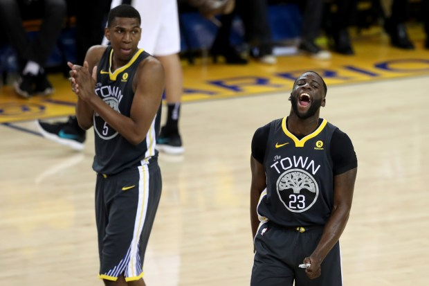 Golden State Warriors' Kevon Looney (5) and Draymond Green (23) react after San Antonio Spurs' Davis Bertans (42) missed a basket on technical foul against Green during the fourth quarter of Game 2 of their NBA first-round playoff series at Oracle Arena in Oakland, Calif., on Monday, April 16, 2018.(Ray Chavez/Bay Area News Group)