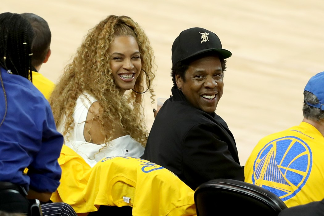 Beyonce, left, and her husband Jay-Z sit on the front row of the court to watch the Golden State Warriors and the  New Orleans Pelicans in Game 1 of the NBA Western Conference semifinals at Oracle Arena in Oakland, Calif., on Saturday, April 28, 2018.(Ray Chavez/Bay Area News Group)