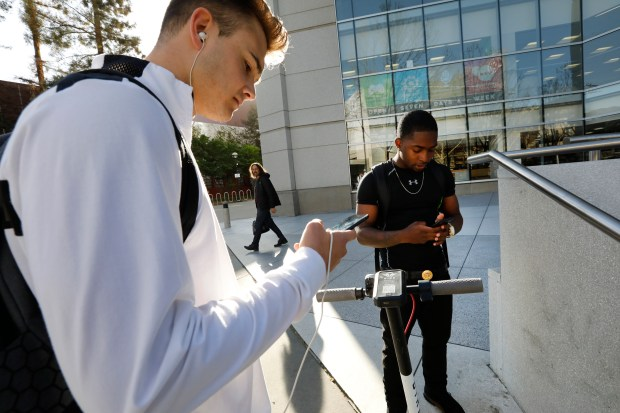 Marko Macura, 20, left, logs in to the BIRD app as Benjamin Quinn, 21, unlocks the BIRD electric scooter after parking it at the Dr. Martin Luther King, Jr. Library in San Jose, Calif., on Tuesday, April 3, 2018. Bike and scooter-sharing companies are flooding San Jose and other Bay Area cities with dock-less bikes and scooters, including electric ones. (Laura A. Oda/Bay Area News Group)