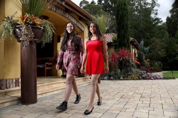 Riya Gupta, 16, left, and Nishka Ayyar, 17, of Saratoga, pose with prom dresses at Ayyar's home in Saratoga, Calif., on Wednesday, April 18, 2018. The students, both juniors at The Harker School in San Jose, Calif., built the PromElle app to allow teens to rent and lend prom and formal dresses. (Ray Chavez/Bay Area News Group)