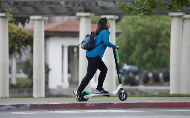 A patron takes off on a Lime-S electric scooter at Lake Merritt off Gand Avenue in Oakland, Calif., on Tuesday, April 10, 2018. (Laura A. Oda/Bay Area News Group)