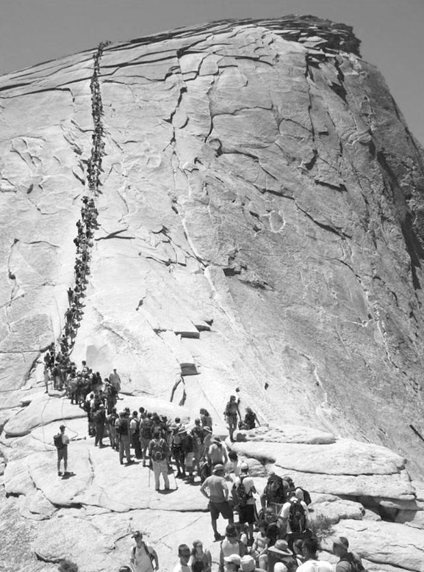 2006 photo: Hikers wait to climb the cables to Half Dome's summit at Yosemite National Park, Calif. (AP photo/National Park Service)