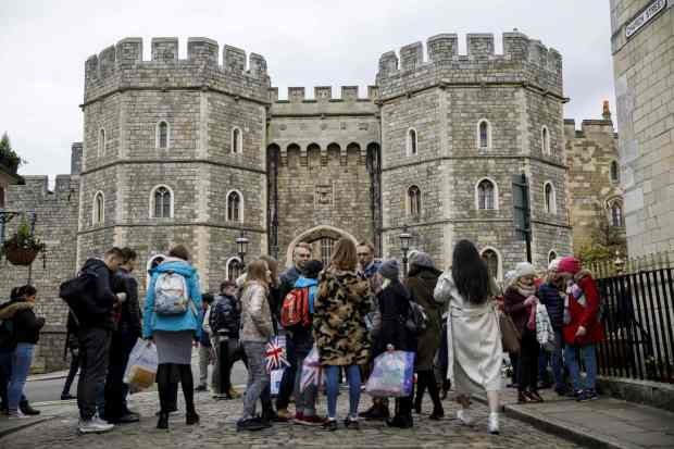 (FILES) In this file photo taken on April 01, 2018 Tourists wait outside the main entrance of Windsor Castle in Windsor, west of London on April 1, 2018.Britain's Prince Harry and US actress Meghan Markle will marry on May 19 at St George's Chapel in Windsor Castle. / AFP PHOTO / Tolga AkmenTOLGA AKMEN/AFP/Getty Images