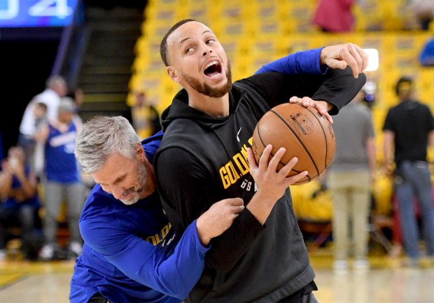 Golden State Warriors' Stephen Curry (30) warms up with assistant coach Bruce Fraser before the start of their NBA Western Conference semifinals game against the New Orleans Pelicans at Oracle Arena in Oakland, Calif., on Tuesday, May, 1, 2018. (Doug Duran/Bay Area News Group)