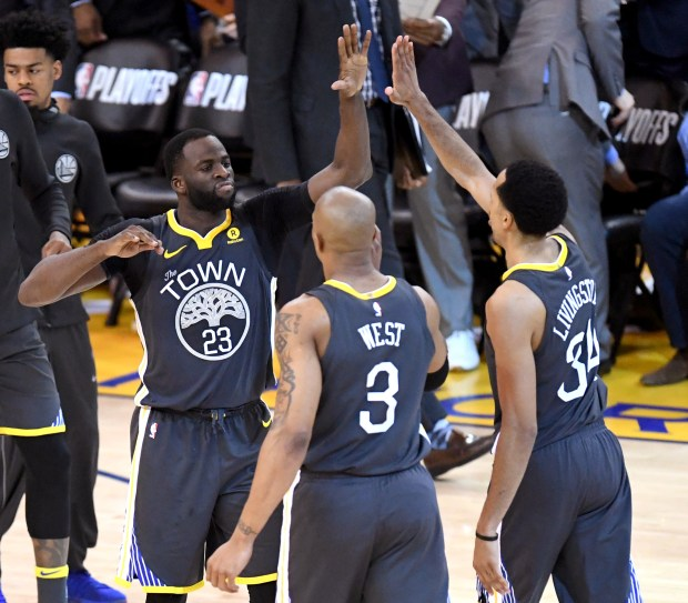 Golden State Warriors' Draymond Green (23) celebrates with Golden State Warriors' David West (3) and Golden State Warriors' Shaun Livingston (34) in the fourth period of their NBA Western Conference semifinals game against the New Orleans Pelicans at Oracle Arena in Oakland, Calif., on Tuesday, May 1, 2018. (Doug Duran/Bay Area News Group)