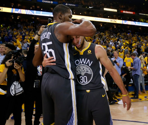 Golden State Warriors' Kevin Durant (35) hugs Golden State Warriors' Stephen Curry (30) following the Warriors 121-116 win over the New Orleans Pelicans for Game 2 of the NBA Western Conference semifinals at Oracle Arena in Oakland, Calif., on Tuesday, May 1, 2018. (Nhat V. Meyer/Bay Area News Group)