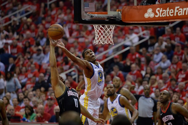 Golden State Warriors' Kevon Looney (5) battles Houston Rockets' Eric Gordon (10) for a rebound during the first quarter of Game 1 of the NBA Western Conference finals at Toyota Center in Houston, Texas, on Monday, May 14, 2018. The Golden State Warriors defeated the Houston Rockets 119-106. (Jose Carlos Fajardo/Bay Area News Group)