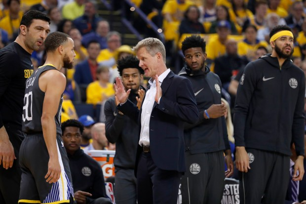 Golden State Warriors' head coach Steve Kerr talks with Stephen Curry (30) in the first quarter of Game 4 of the NBA Western Conference finals against the Houston Rockets at Oracle Arena in Oakland, Calif., on Tuesday, May 22, 2018.