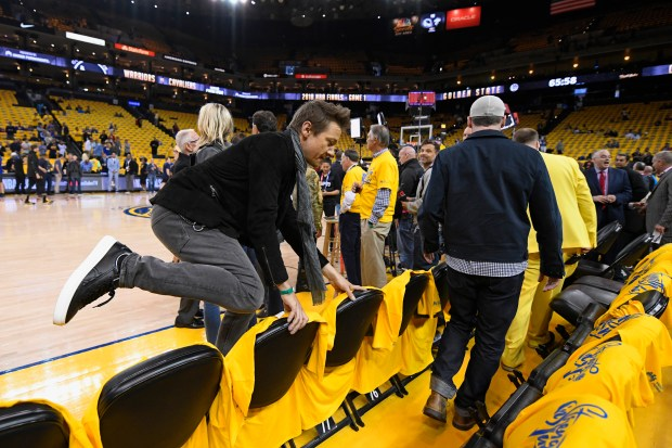 Actor Jeremy Renner leaps a row of chairs courtside before Game 1 of the NBA Finals at Oracle Arena in Oakland, Calif., on Thursday, May 31, 2018. (Jose Carlos Fajardo/Bay Area News Group)