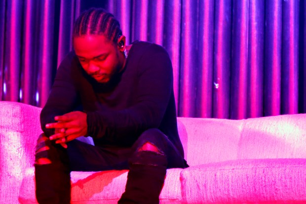 Kendrick Lamar appears seated on a couch at the start of his show at the Fox Theater in Oakland, Calif., on Tuesday, Nov. 10, 2015. (Ray Chavez/Bay Area News Group)