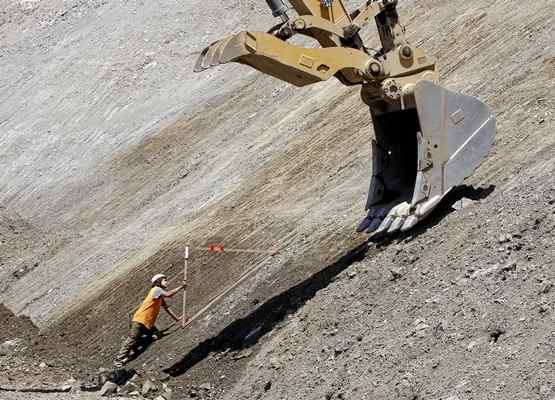 Jesse Foster uses a 45-degree form to monitor the work being done by a heavy machine operator as work continues at the Mud Creek slide on Highway 1 south of Big Sur on Monday. (Vern Fisher - Monterey Herald)