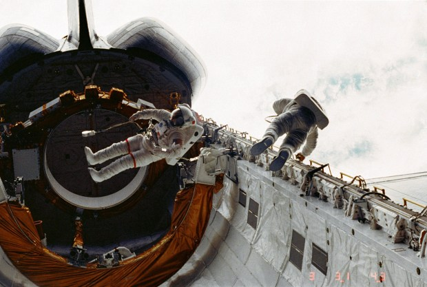 Don Peterson, on the right, floats in the cargo bay of the Challenger space shuttle. CREDIT: NASA handbill