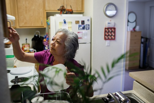 Portrait: Teri Bruner puts away dishes in her new home at an affordable residence for seniors, Gateway Santa Clara, on April 19, 2018. In 2016, Bruner, then 72, was evicted from the house in San Jose she had rented for 19 years after the owner decided to sell it. With no place to go, she and her boyfriend became homeless. They stayed in motels until they ran out of money, and then lived out of a van. (Dai Sugano/Bay Area News Group)