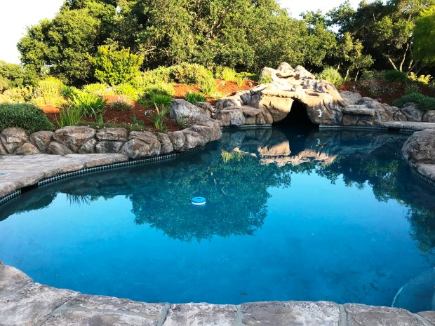 The backyard amenities include this gorgeous pool and spa, plus a full tennis court and sports court.