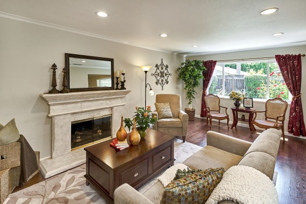 The Campbell home's living room features a gas fireplace with stone surround and large windows.