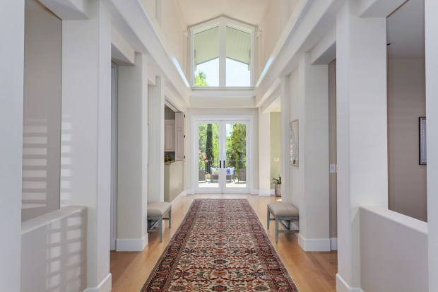 French doors at the end of the long hall entice you with a view of the backyard oasis.