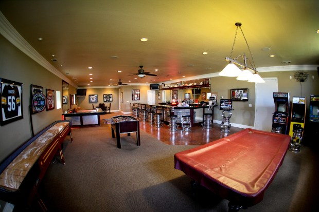 The man cave includes sports memorabilia, a pool table, shuffleboard, video games and full-length bar.