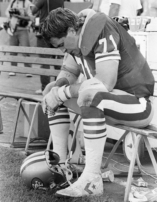 San Francisco 49ers tackle Keith Fahnhorst looks dejected sitting on the bench in the fourth quarter during the 49ers 26-10 loss to the Chicago Bears at Candlestick Park in San Francisco, Oct. 14, 1985. (AP Photo/Eric Risberg)