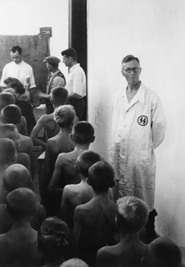 """Poland: 1942. Checking Polish children for 'Lebensborn'. By order of the Reich SS Leader, Heinrich Himmler, during the war the task was given to the 'Lebensborn' organization to look in the eastern areas occupied by Germany for 'racially flawless northern' children. SS doctors checking Polish children for the 'Lebensborn'. Poland ©SZ Photo / Scherl / The Image Works NOTE: The copyright notice must include """"The Image Works"""" DO NOT SHORTEN THE NAME OF THE COMPANY"""