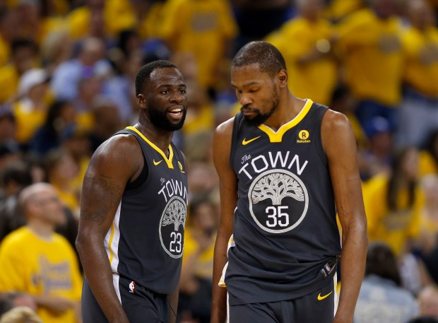 Golden State Warriors' Draymond Green (23) and Kevin Durant (35) talk during the third quarter of Game 2 of the NBA Finals against the Cleveland Cavaliers at Oracle Arena in Oakland, Calif., on Sunday, June 3, 2018. (Nhat V. Meyer/Bay Area News Group)