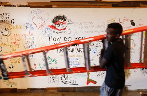 Morris Black moves a ladder through one of the rooms with a wall of free expression as he helps to set up the art space for an event at the Alena Museum in Oakland, Calif., on Friday, June 15, 2018. The Alena Museum, an art gallery dedicated to supporting work that reflects on the African diaspora, is fighting to keep its space in fast-gentrifying West Oakland. (Laura A. Oda/Bay Area News Group)