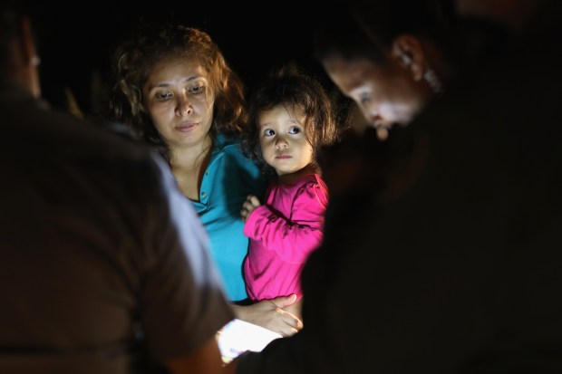 MCALLEN, TX - JUNE 12: Central American asylum seekers, including a Honduran girl, 2, and her mother, are taken into custody near the U.S.-Mexico border on June 12, 2018 in McAllen, Texas. The group of women and children had rafted across the Rio Grande from Mexico and were detained by U.S. Border Patrol agents before being sent to a processing center for possible separation. Customs and Border Protection (CBP) is executing the Trump administration's zero tolerance policy towards undocumented immigrants. U.S. Attorney General Jeff Sessions also said that domestic and gang violence in immigrants' country of origin would no longer qualify them for political asylum status. (Photo by John Moore/Getty Images)