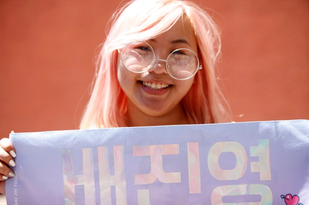 Rin Nguyen holds up a poster while waiting in line for a Wanna One concert, Thursday, June 21, 2018 at San Jose State University. (Mya Hammond/Mosaic)