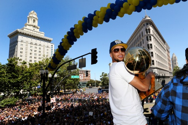 Golden State Warriors' Stephen Curry holds the Larry O'Brien NBA Championship Trophy as he rides on a double decker bus during the Warriors championship parade in downtown Oakland, Calif., on Tuesday, June 12, 2018. (Ray Chavez/Bay Area News Group)