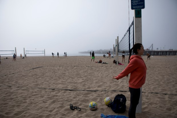Emily Melvin, 16, right, stretches before playing volleyball on the beach in Santa Cruz, Calif., on Thursday, June 21, 2018. A bill to make surfing the official sport of California is finding little resistance as it heads for a state Senate hearing. Some people like Melvin feel beach volleyball should be the Golden State's official sport. (Randy Vazquez/ Bay Area News Group)