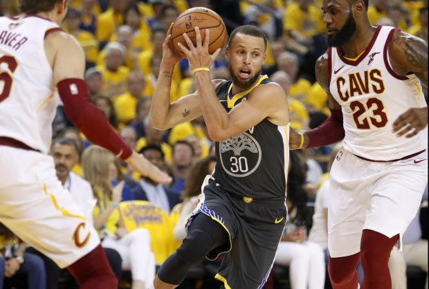 Golden State Warriors' Stephen Curry (30) drives past Cleveland Cavaliers' LeBron James (23) and Kyle Korver (26) during the first quarter of Game 2 of the NBA Finals at Oracle Arena in Oakland, Calif., on Sunday, June 3, 2018. (Nhat V. Meyer/Bay Area News Group)