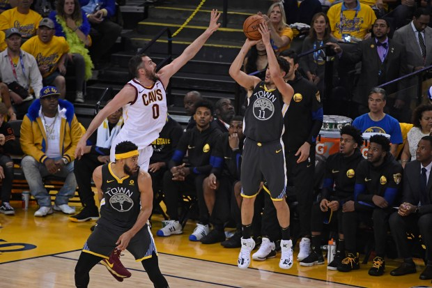 Golden State Warriors' Klay Thompson (11) shoots and makes a 3-point basket over Cleveland Cavaliers' Kevin Love (0) during the first quarter of Game 2 of the NBA Finals at Oracle Arena in Oakland, Calif., on Sunday, June 3, 2018. (Jose Carlos Fajardo/Bay Area News Group)