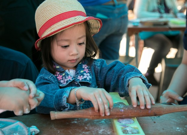 """Sophia Tran, 2, of San Jose makes a Vietnamese jello dessert out of play dough at the """"A Seat at the Table"""" pop-up installation at the Children's Discovery Museum in San Jose, California on Saturday, June 2, 2018. (LiPo Ching/Bay Area News Group)"""