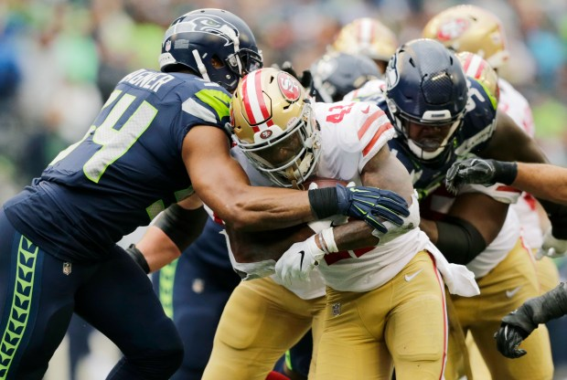 41a966cec San Francisco 49ers running back Jeff Wilson is tackled by Seattle Seahawks  middle linebacker Bobby Wagner