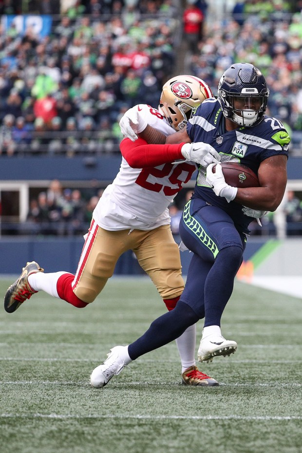 cfeac71d2 Rashaad Penny  20 of the Seattle Seahawks tries to avoid a tackle by  Jaquiski Tartt  29 of the San Francisco 49ers in the second quarter at  CenturyLink ...