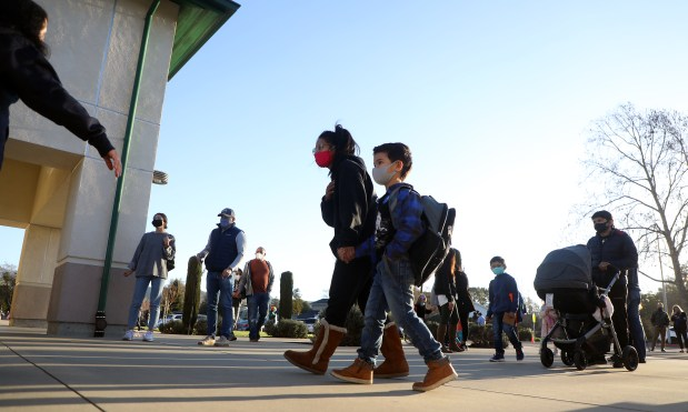DANVILLE, CA - FEBRUARY 10: Nicole Clupny, center, walks her son Titan ,5, to the entrance of Greenbrook Elementary School on Wednesday, Feb. 10, 2021, in Danville, Calif. The San Ramon Unified School District reopened classrooms to students in a multi-phase, hybrid plan, and expects to see 10,000 students in grades pre-kindergarten through 6th grade return to campuses by next Wednesday. (Aric Crabb/Bay Area News Group)