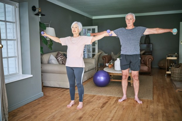 Senior couple lifting dumbbells while working out at home