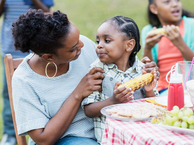 Mother And Son Smiling And Eating Roasted Corn On The Cob