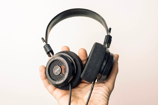 Hand holding a large set of headphones for listening to podcasts