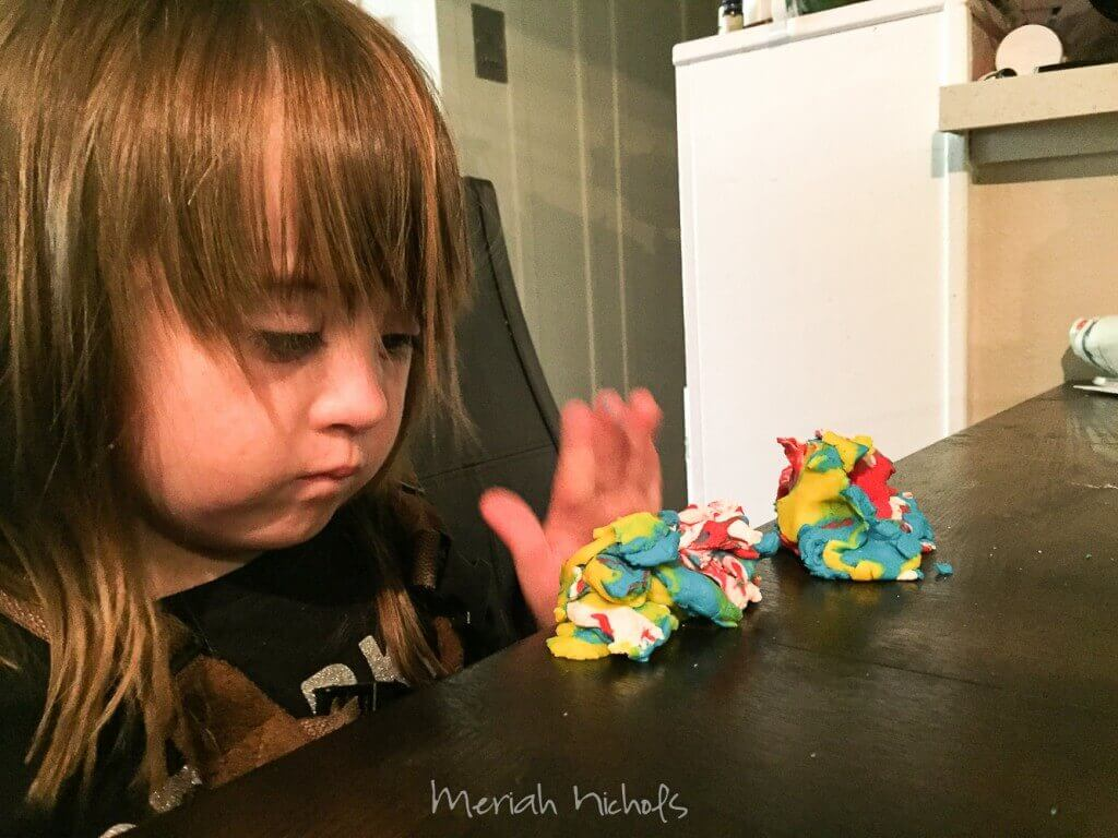 small child - Moxie - channeling her inner Judith Scott by playing stacking and arranging bits of coloured playdough in designs