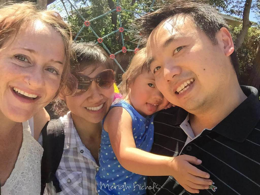 attractive Asian couple with beautiful young daughter, white woman (= me) with remarkably natural teeth smiles from the left